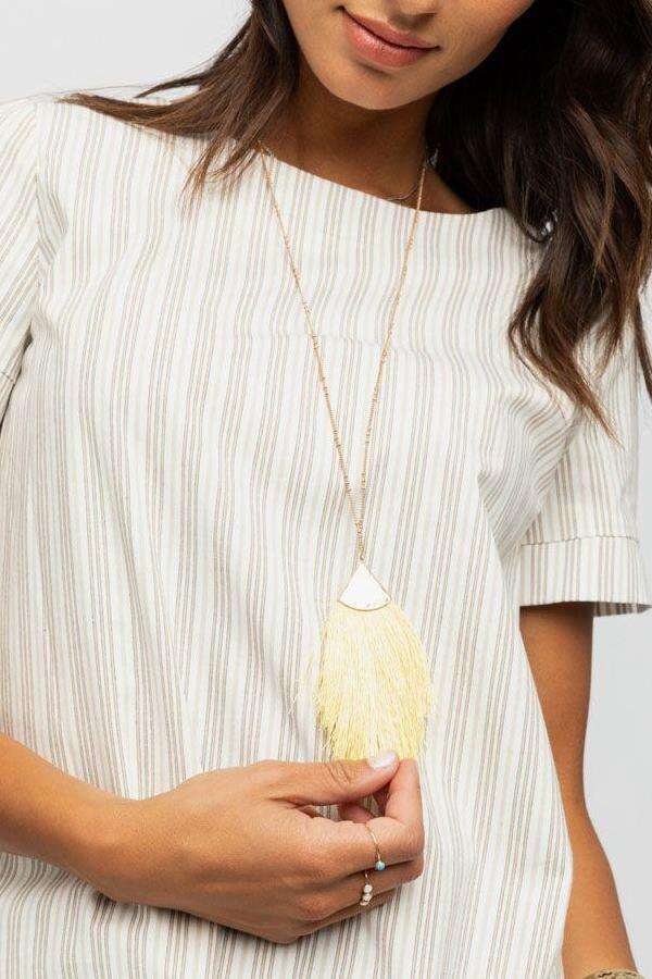 Lovely golden tassel necklace! Pair it with a top in ivory to make a chic look.